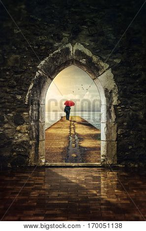 Stone wall and gothic door to a pier with a man and red umbrella