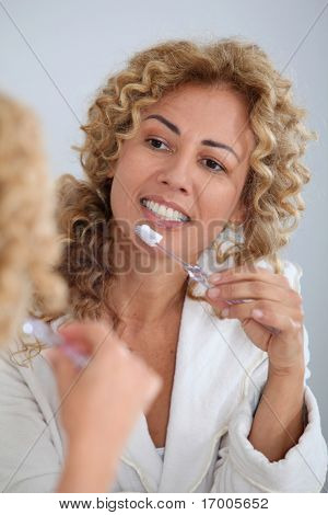Portrait of woman brushing her teeth in front of mirror