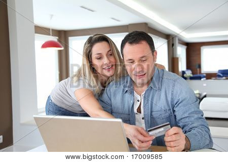 Couple doing online shopping with laptop computer