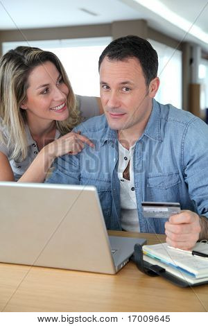 Couple doing online shopping wih laptop computer