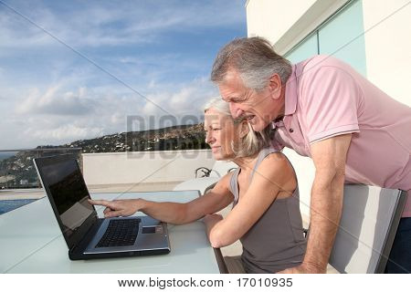Senior couple sitting outside with laptop computer