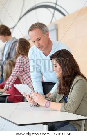 Teacher and teenage girl working on electronic tablet