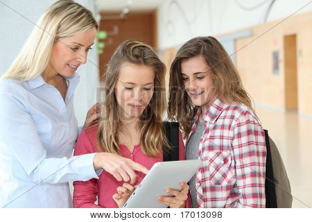 Teacher and teenage girls using electronic tablet