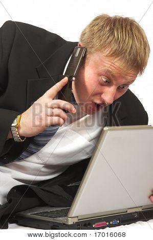 El empresario con teléfono busca en portátil. Pruebas de un susto y la sorpresa.