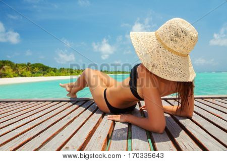 poster of Young fashion woman relax on the beach. Happy island lifestyle. White sand, blue cloudy sky and crys