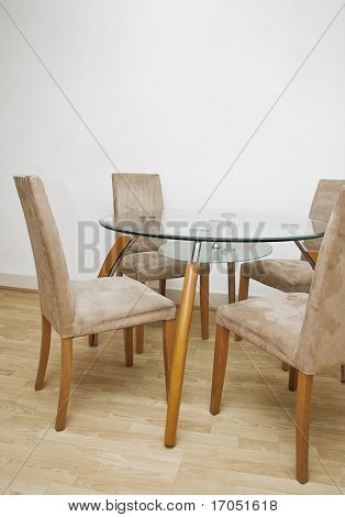 detail of a glass top dining table with four chairs