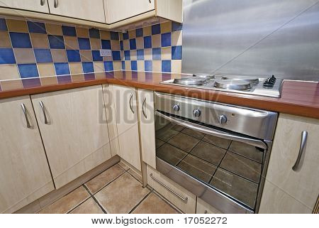 kitchen with wooden worktop and checked yellow and blue ceramic tiles