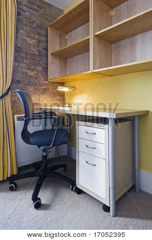 home office with chair, desk, drawers and exposed brick work