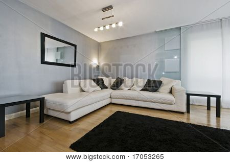 detail of a white leather corner sofa in a living room with blue metallic wall paint