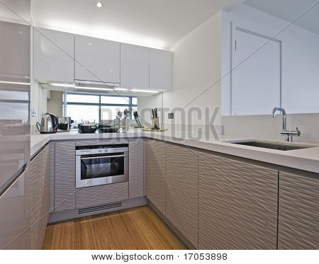 ultra modern kitchen counter with white stone worktop and appliances