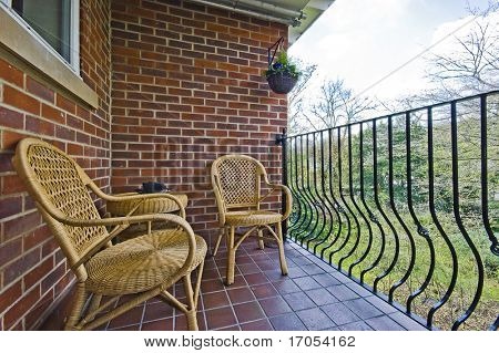 cozy balcony with rattan chair and table over a park