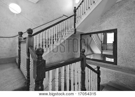 victorian wooden staircase with carved rails and decoration in black and white