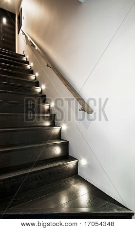 wooden staircase with spotlights and metallic rail