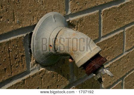 Rusty Spigot On Brick Wall