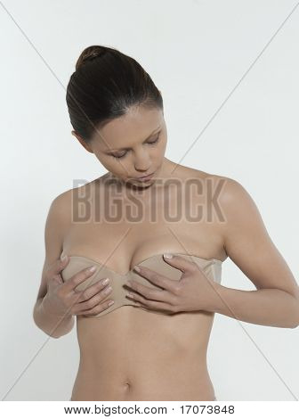 asian woman on isolated background looking at her breast