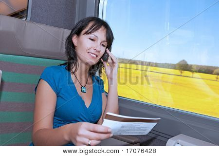 beautiful young woman  in a train making a phone call  with a ticket in his han