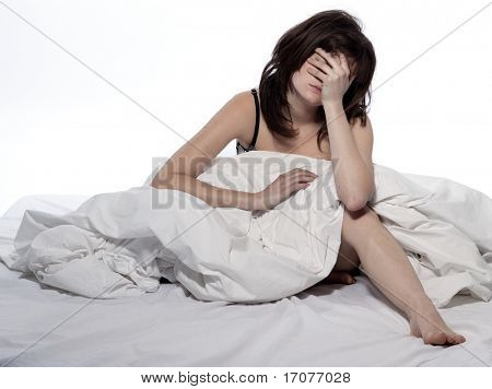 young woman in a white sheet bed on white background