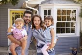 Portrait Of Excited Family Standing Outside New Home poster