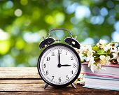 Alarm clock with books and spring blooming branch on wooden table against foliage background. Time c poster