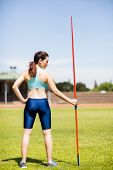 Постер, плакат: Rear view of female athlete holding a javelin in stadium on a sunny day