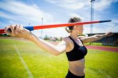 Постер, плакат: Female athlete about to throw a javelin in the stadium