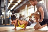 Fitness instructor with girl on training in fitness center poster