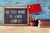 a chalkboard with the question do you want to learn chinese?, a pot with pencils, some old books and poster