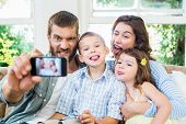 Happy family taking a selfie on mobile phone in living room poster