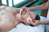 Man receiving a facial massage from masseur in spa poster