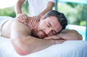 Man receiving back massage from masseur in spa poster