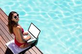Woman using her laptop on the pool edge on a sunny day poster