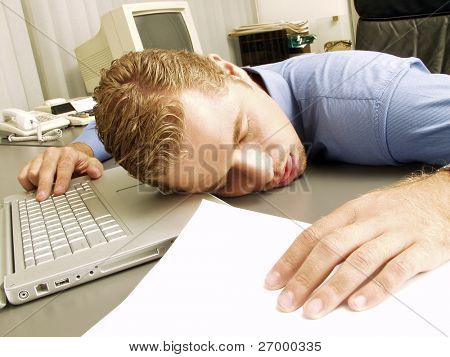 exhausted young businessman sleeping at his desk.