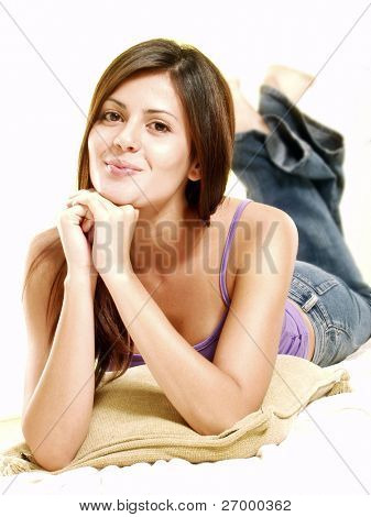 Relaxed young woman on white over a cushion.