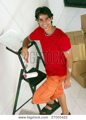 Young hispanic man moving to a new home. Young hispanic man painting a new home.