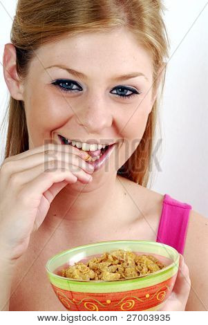 Young woman eating and holding a cereal bowl.