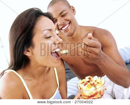 Young hispanic couple enjoying and eating fruit salad on bed.