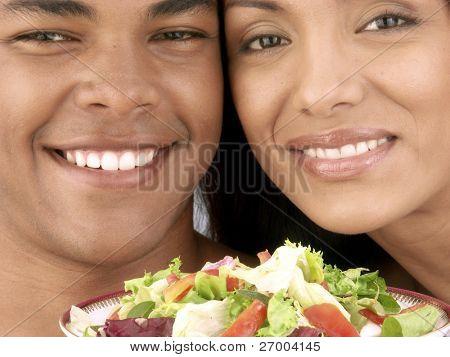 Young hispanic couple enjoying and eating vegetable salad on white background.