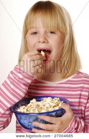 Menina comendo pipoca. Little kid comendo pipoca.