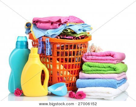 Clothes with detergent and washing powder in orange plastic basket isolated on white