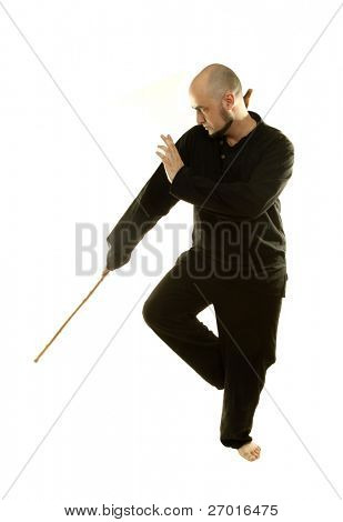 Tai Chi chuan man is practicing martial art with wooden staff