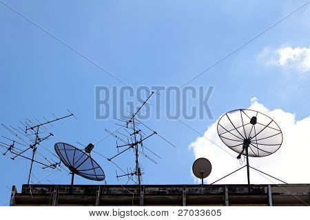 Satellite Dish and radio antenna on top of building