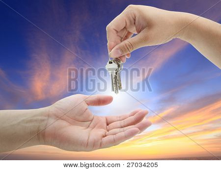 hand giving set of house keys against with twilight background