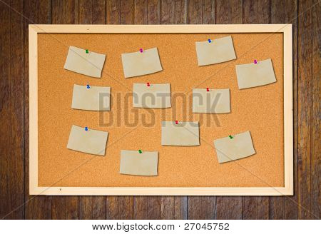 cork bulletin board with old paper note on wood wall