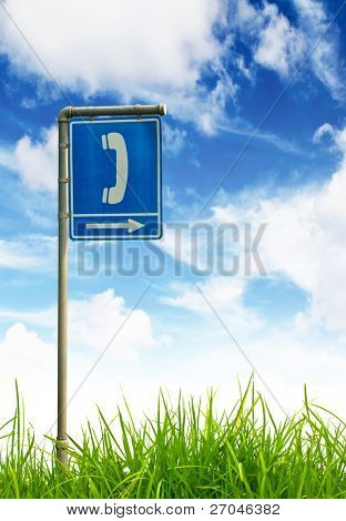 Traffic sign on green grass and blue sky.