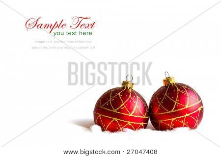 Shiny red christmas balls in billowy feathers with copy space.
