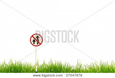 Traffic sign and fresh spring green grass isolated on white background.