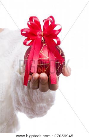 Red christmas ball with red bow in women hand on white background