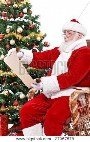 Santa Claus reading wish list, sitting in rocking chair next  Christmas tree, isolated on white background