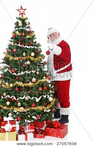 real Santa Claus holding Christmas ball and decorating  Christmas tree, isolated on white background