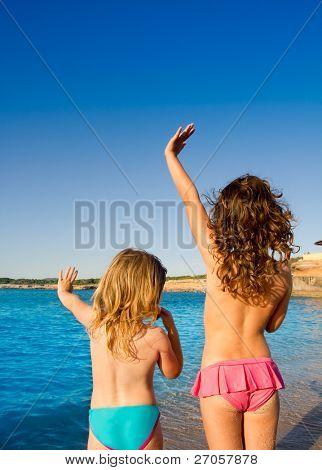Ibiza Cala Conta beach little girls greeting hand sign saying bye